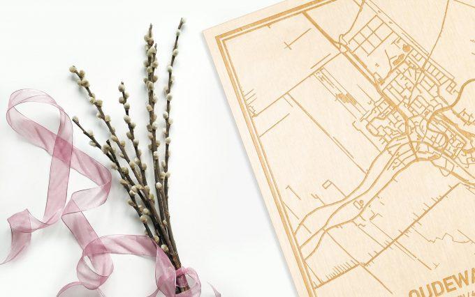 Hier ligt de houten plattegrond Oudewater naast een bloemetje als gepersonaliseerd cadeau voor haar.