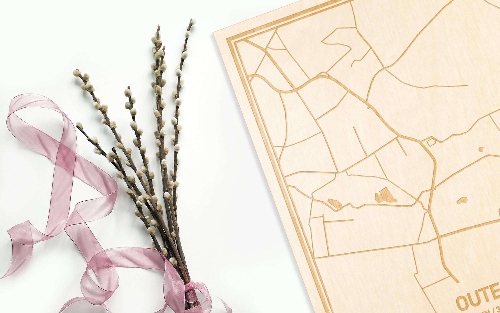 Hier ligt de houten plattegrond Outer naast een bloemetje als gepersonaliseerd cadeau voor haar.