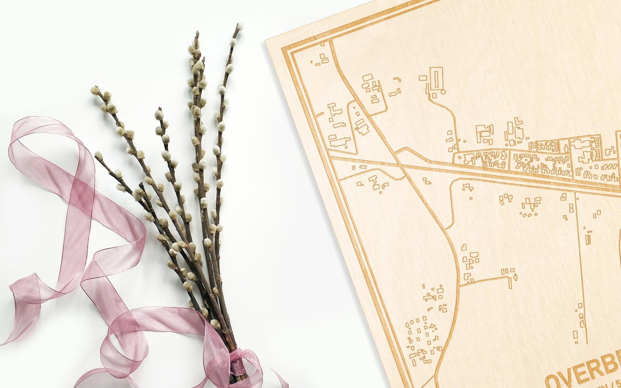 Hier ligt de houten plattegrond Overberg naast een bloemetje als gepersonaliseerd cadeau voor haar.