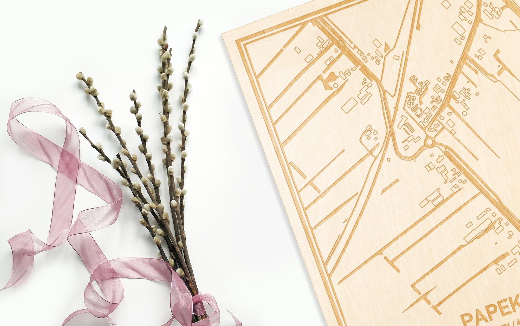 Hier ligt de houten plattegrond Papekop naast een bloemetje als gepersonaliseerd cadeau voor haar.