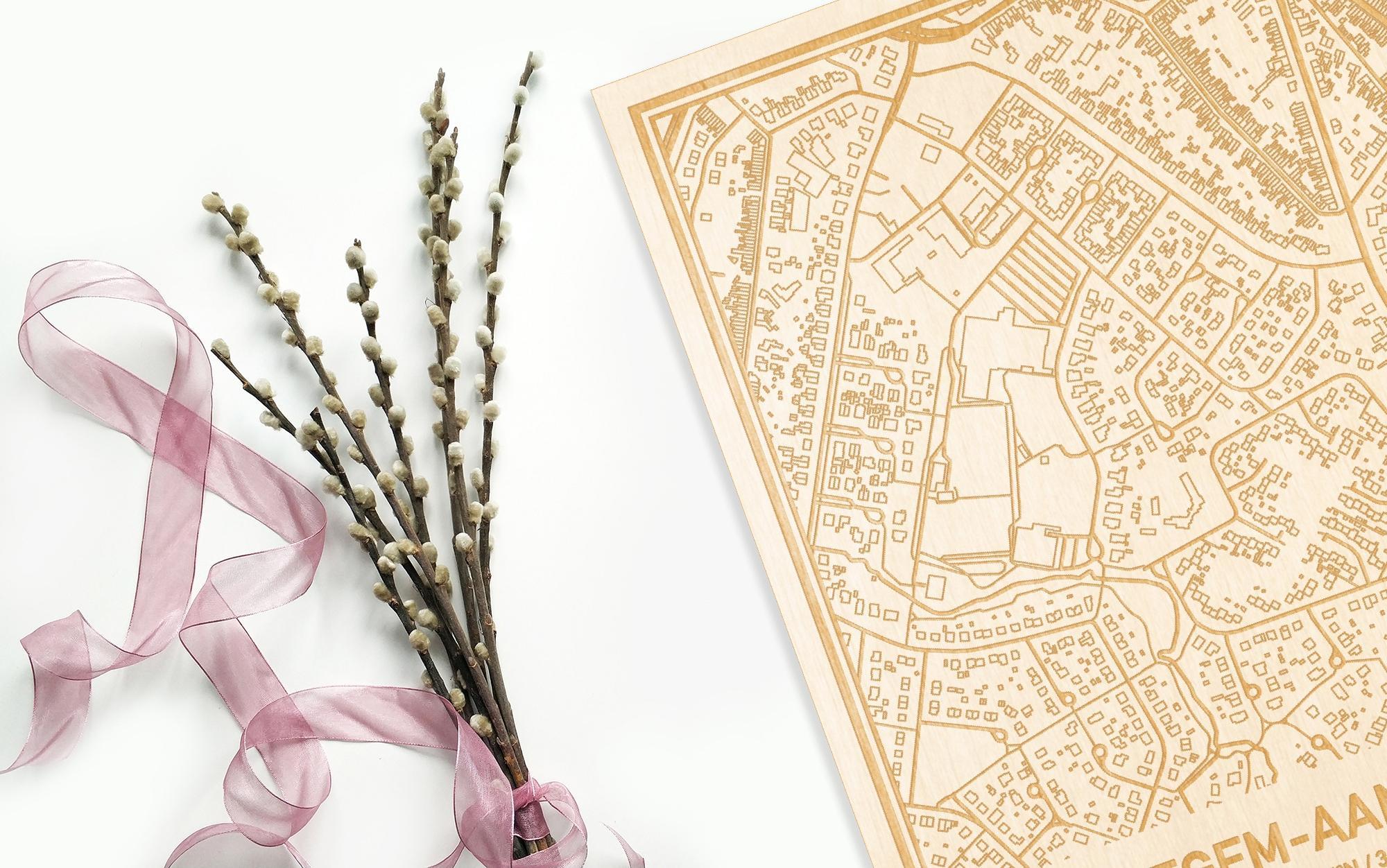 Hier ligt de houten plattegrond Petegem-Aan-De-Leie naast een bloemetje als gepersonaliseerd cadeau voor haar.
