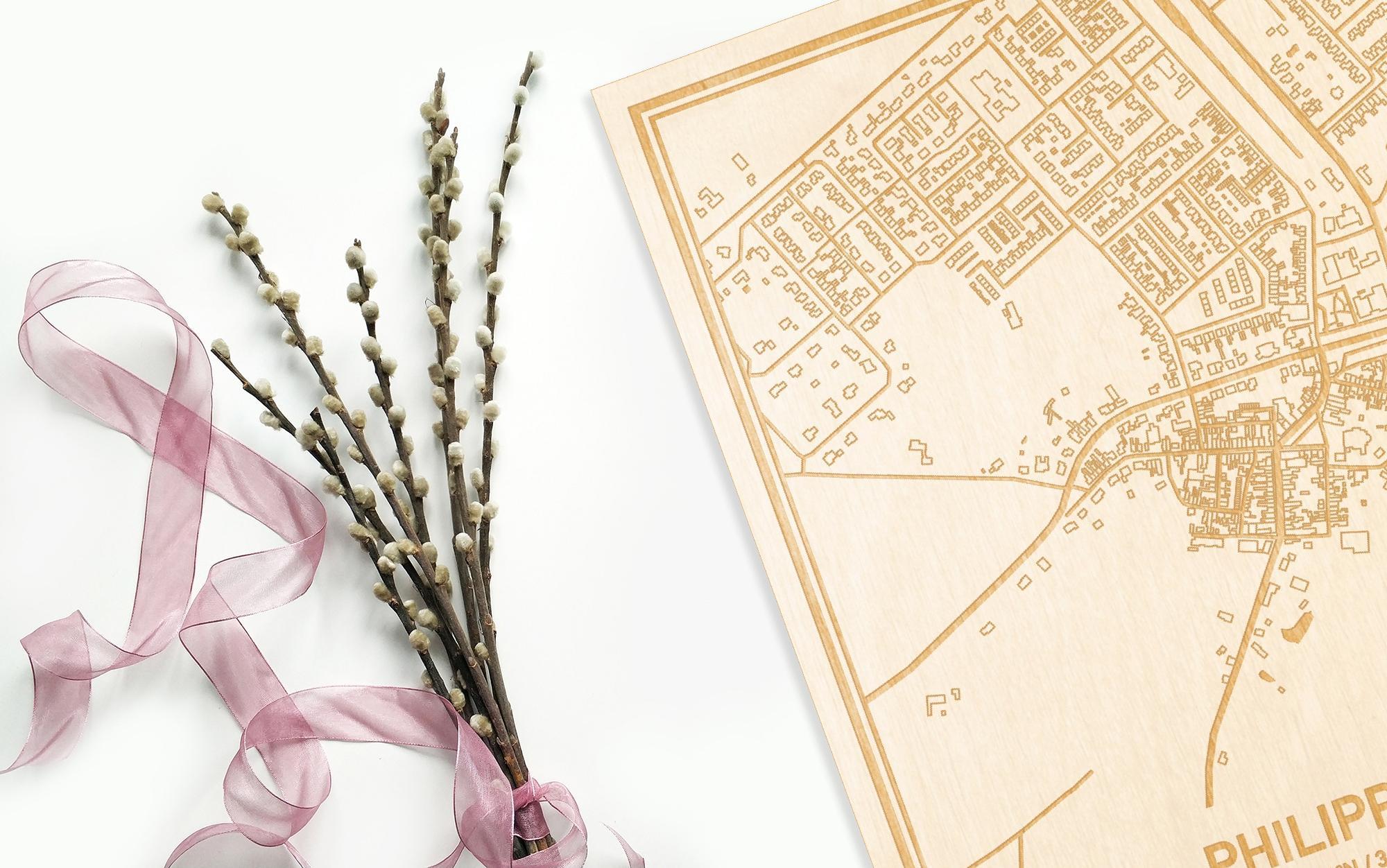 Hier ligt de houten plattegrond Philippine naast een bloemetje als gepersonaliseerd cadeau voor haar.