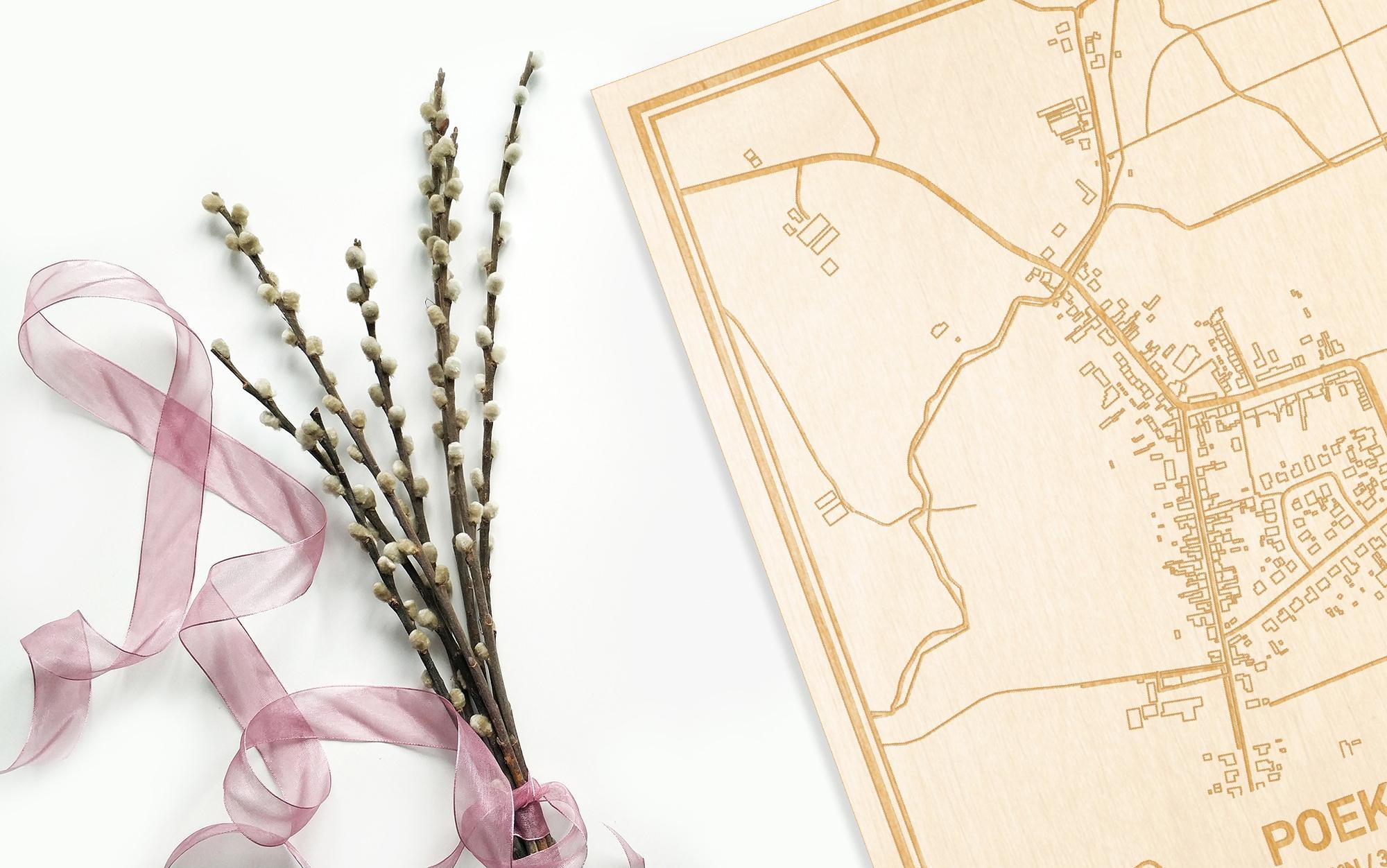 Hier ligt de houten plattegrond Poeke naast een bloemetje als gepersonaliseerd cadeau voor haar.