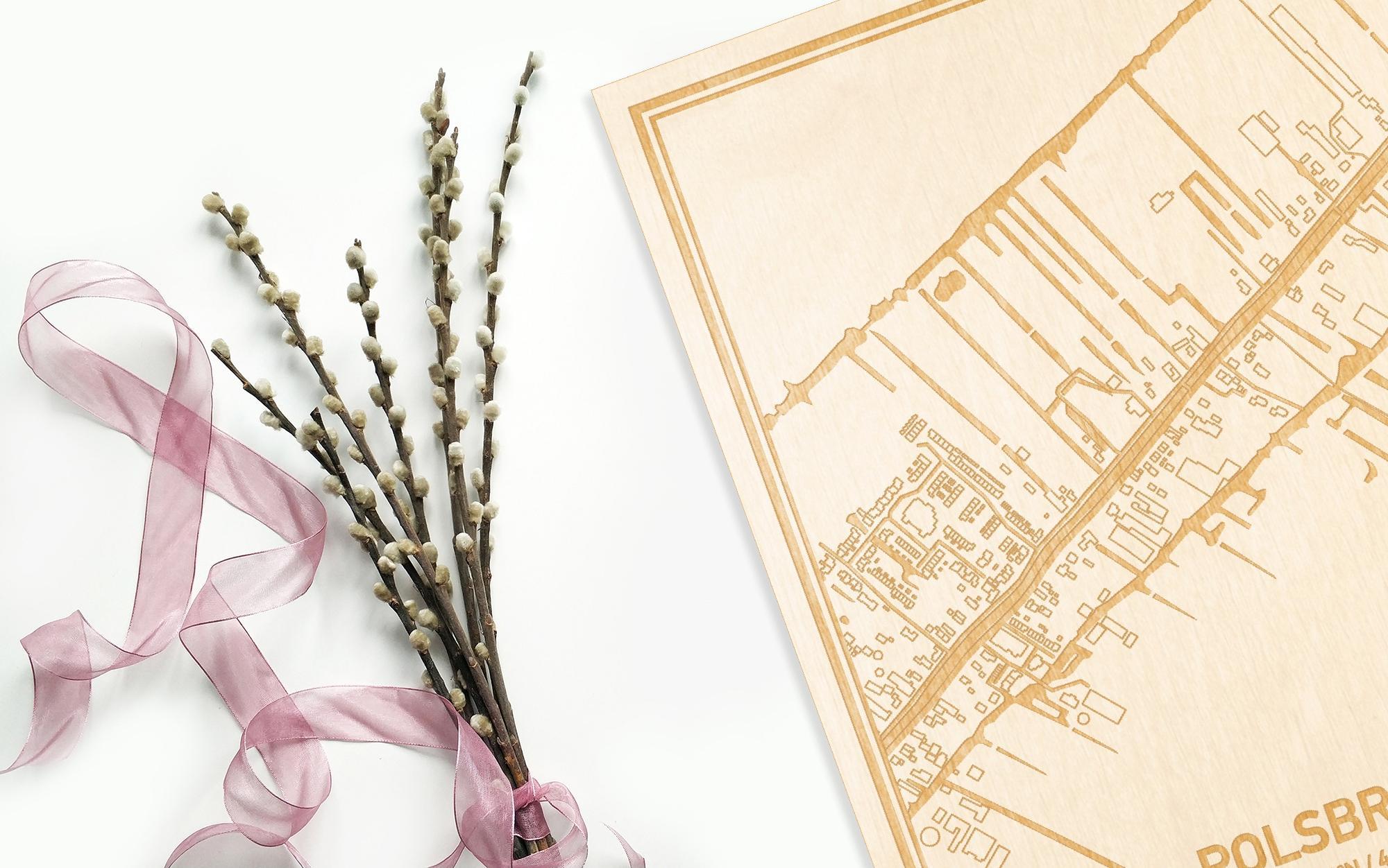 Hier ligt de houten plattegrond Polsbroek naast een bloemetje als gepersonaliseerd cadeau voor haar.