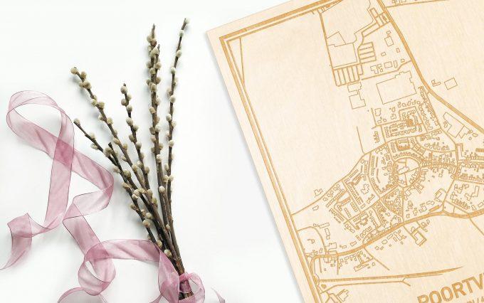 Hier ligt de houten plattegrond Poortvliet naast een bloemetje als gepersonaliseerd cadeau voor haar.