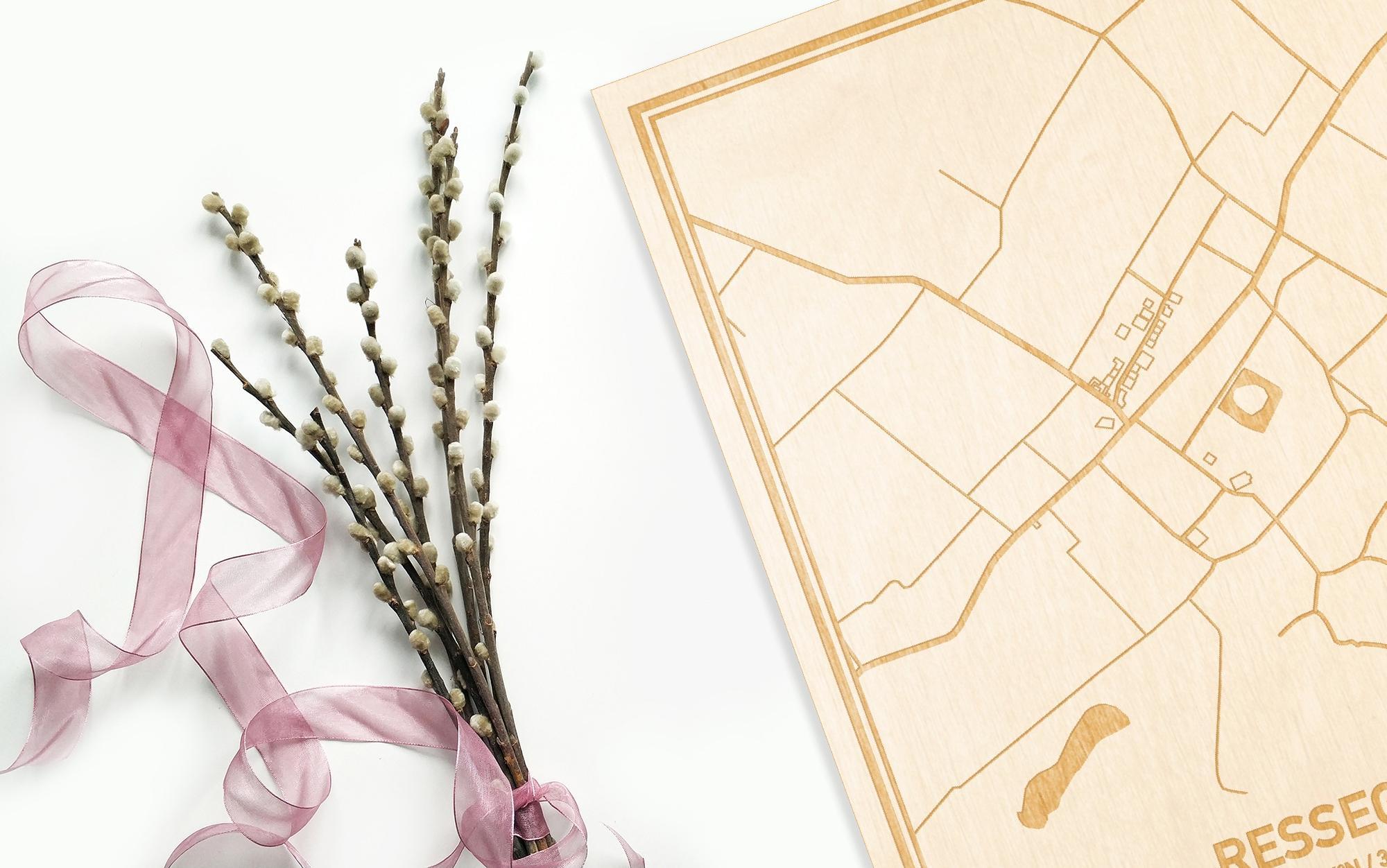 Hier ligt de houten plattegrond Ressegem naast een bloemetje als gepersonaliseerd cadeau voor haar.