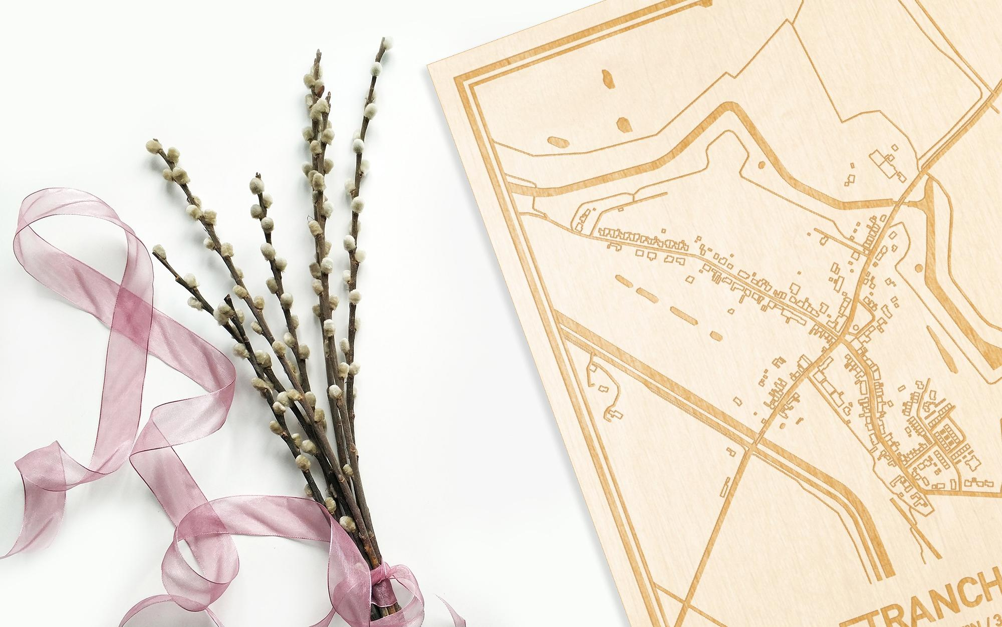 Hier ligt de houten plattegrond Retranchement naast een bloemetje als gepersonaliseerd cadeau voor haar.