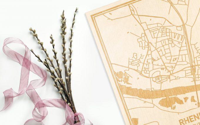 Hier ligt de houten plattegrond Rhenen naast een bloemetje als gepersonaliseerd cadeau voor haar.