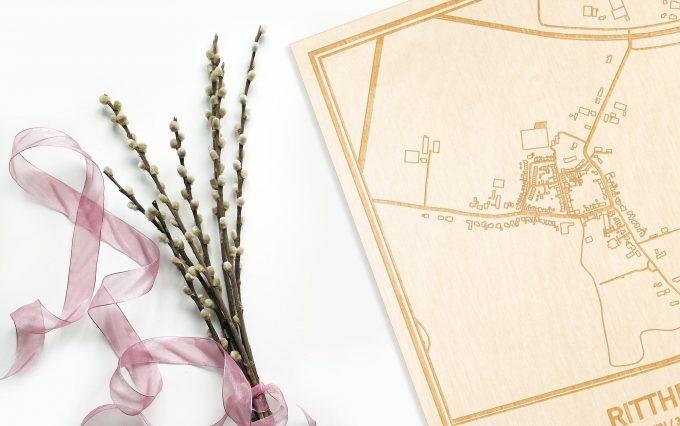 Hier ligt de houten plattegrond Ritthem naast een bloemetje als gepersonaliseerd cadeau voor haar.