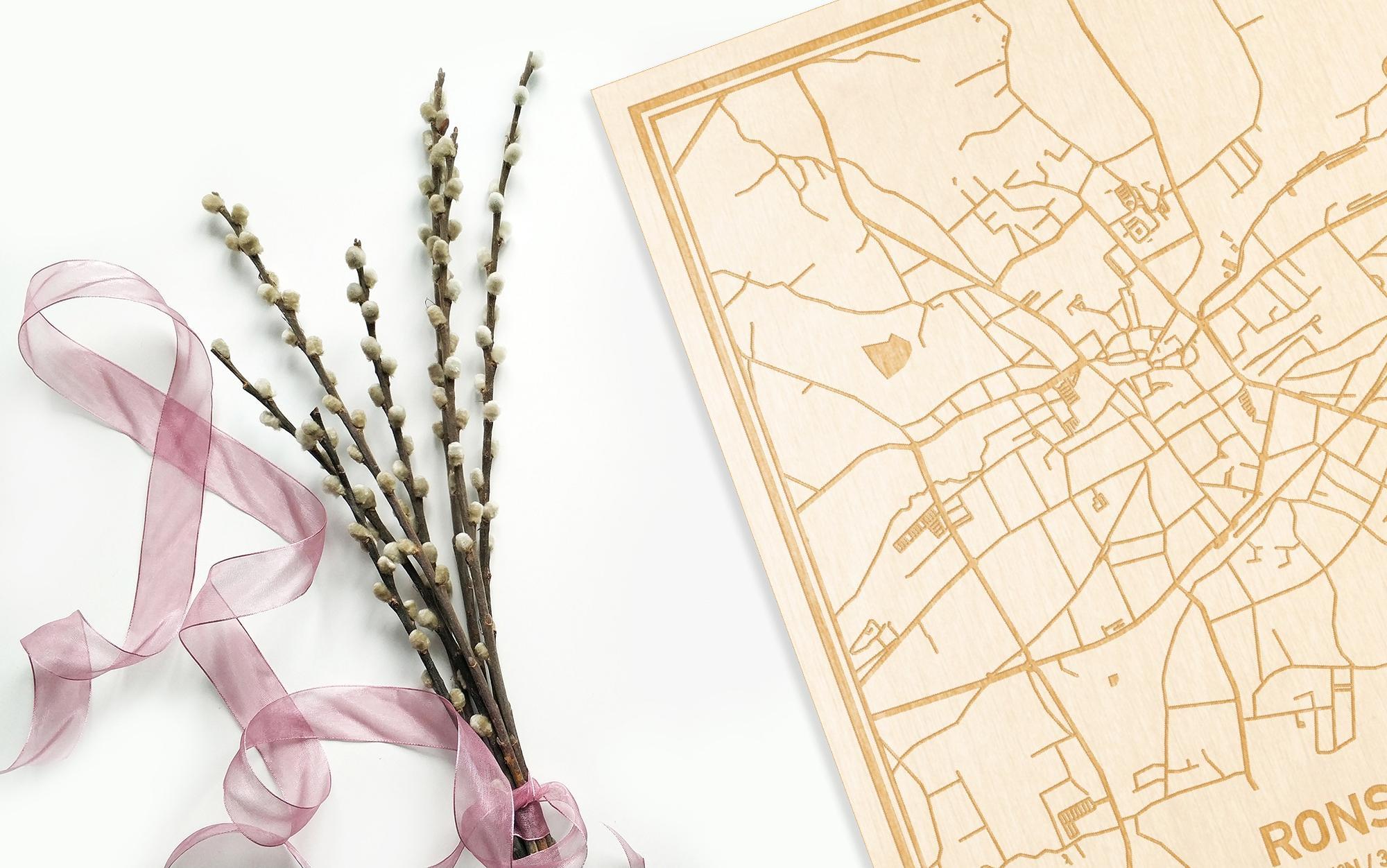 Hier ligt de houten plattegrond Ronse naast een bloemetje als gepersonaliseerd cadeau voor haar.