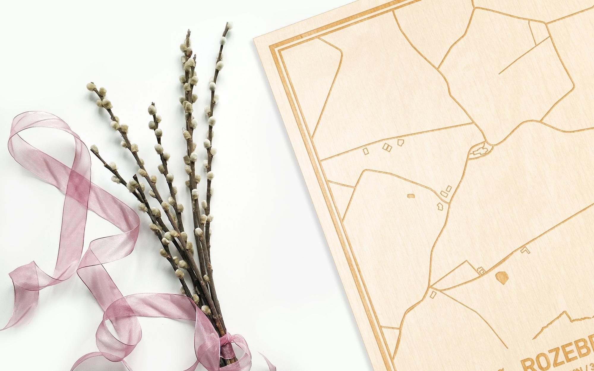 Hier ligt de houten plattegrond Rozebeke naast een bloemetje als gepersonaliseerd cadeau voor haar.