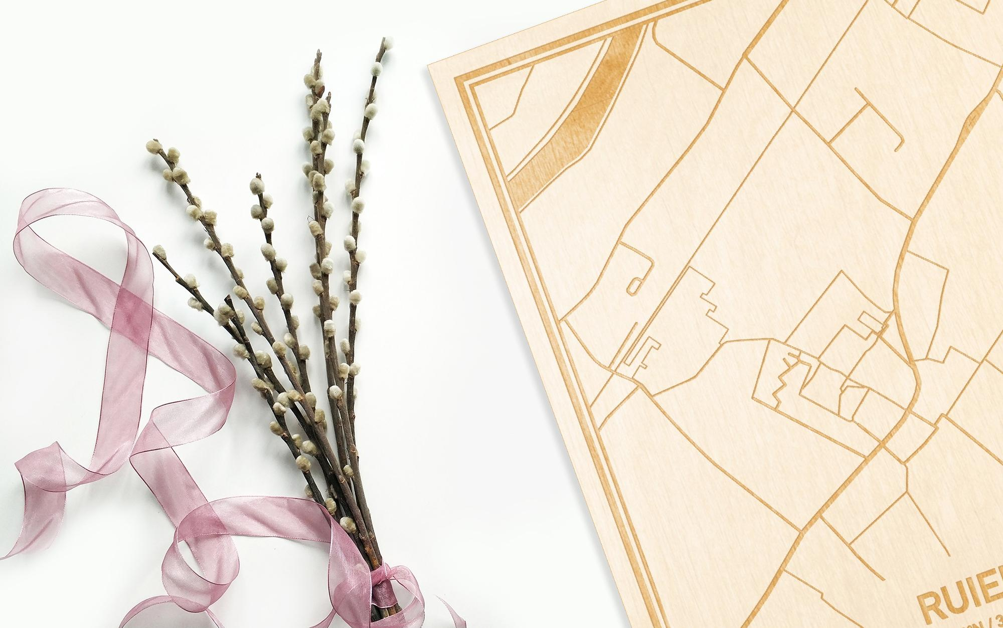 Hier ligt de houten plattegrond Ruien naast een bloemetje als gepersonaliseerd cadeau voor haar.