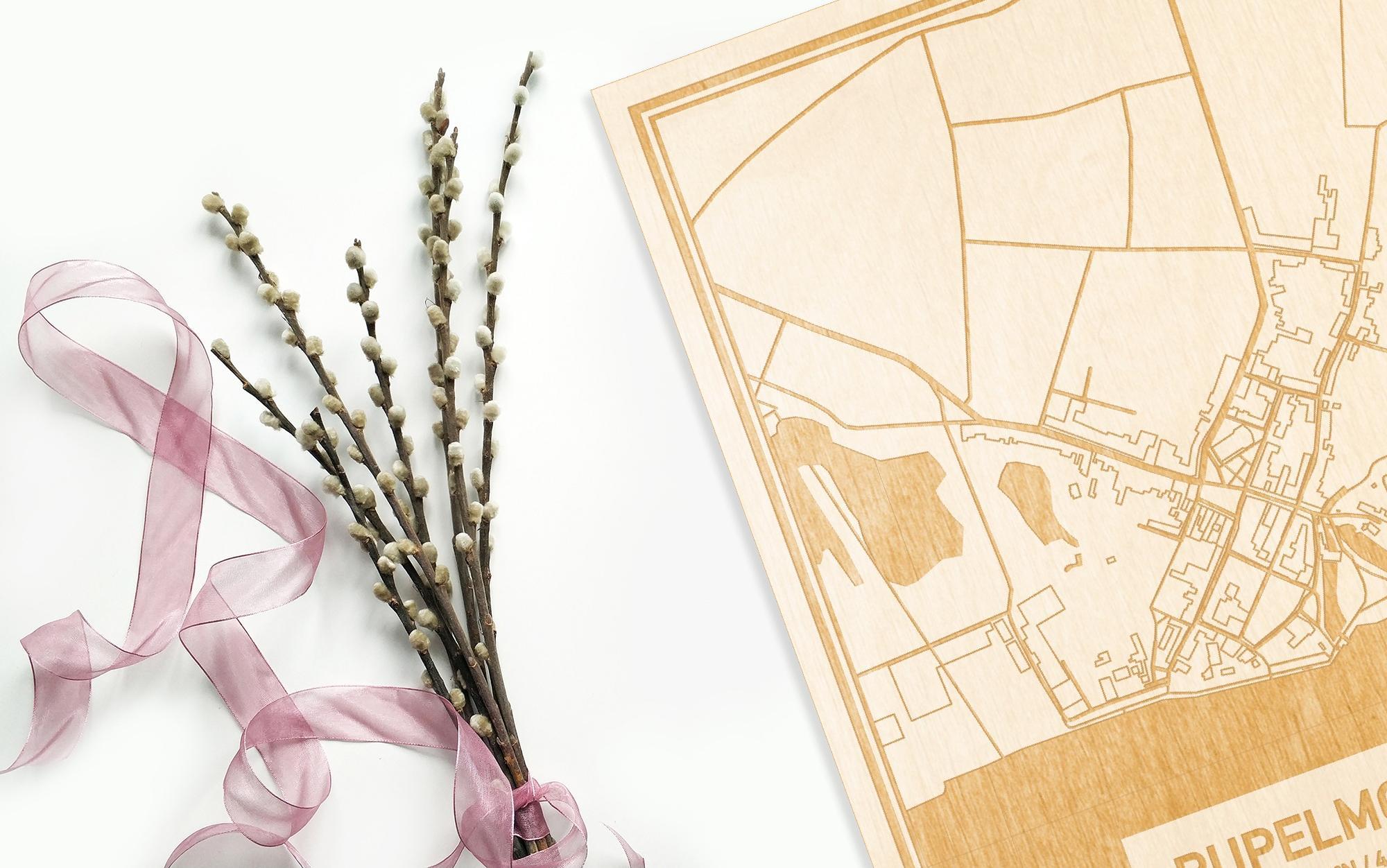 Hier ligt de houten plattegrond Rupelmonde naast een bloemetje als gepersonaliseerd cadeau voor haar.