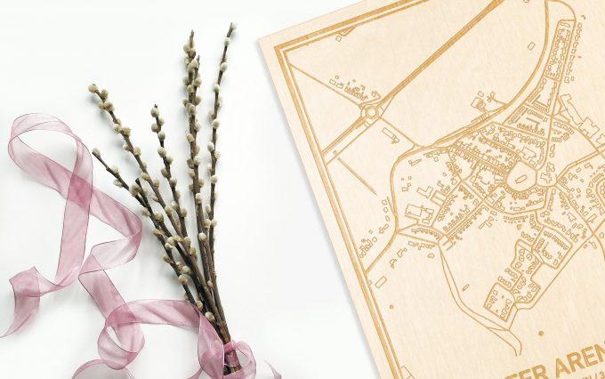 Hier ligt de houten plattegrond 's-Heer Arendskerke naast een bloemetje als gepersonaliseerd cadeau voor haar.