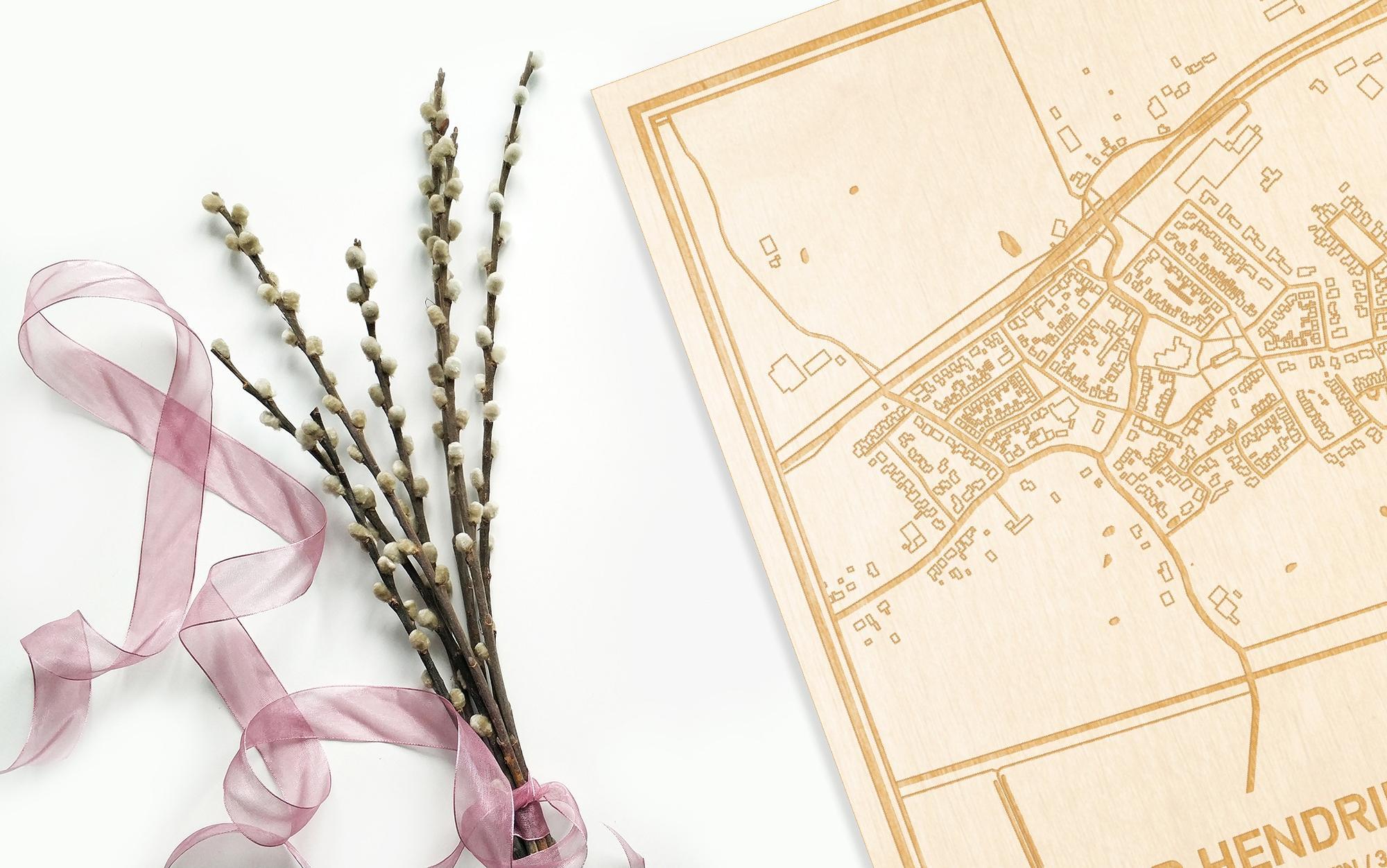 Hier ligt de houten plattegrond 's-Heer Hendrikskinderen naast een bloemetje als gepersonaliseerd cadeau voor haar.