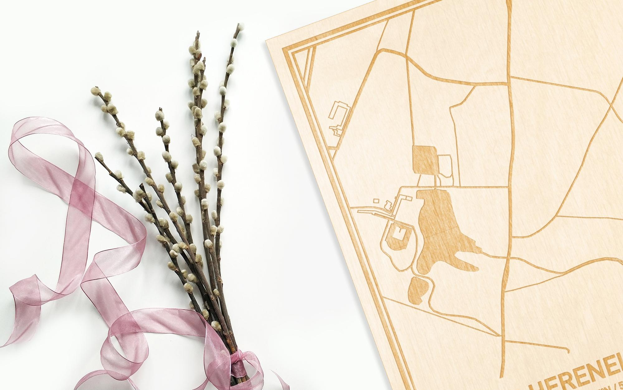 Hier ligt de houten plattegrond 'S Herenelderen naast een bloemetje als gepersonaliseerd cadeau voor haar.