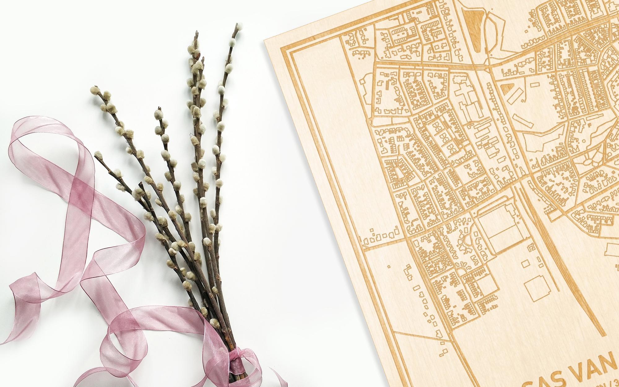 Hier ligt de houten plattegrond Sas van Gent naast een bloemetje als gepersonaliseerd cadeau voor haar.