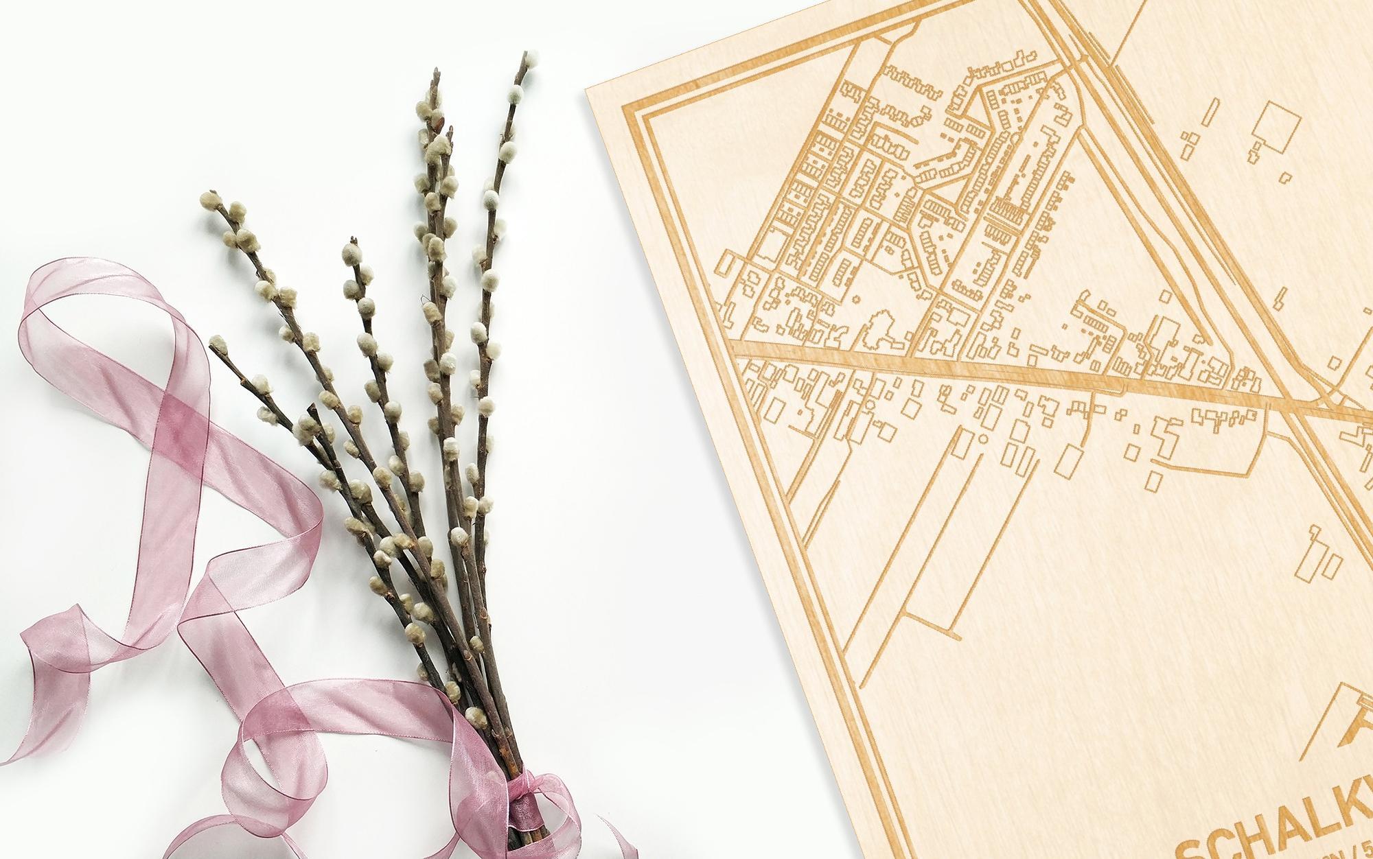 Hier ligt de houten plattegrond Schalkwijk naast een bloemetje als gepersonaliseerd cadeau voor haar.