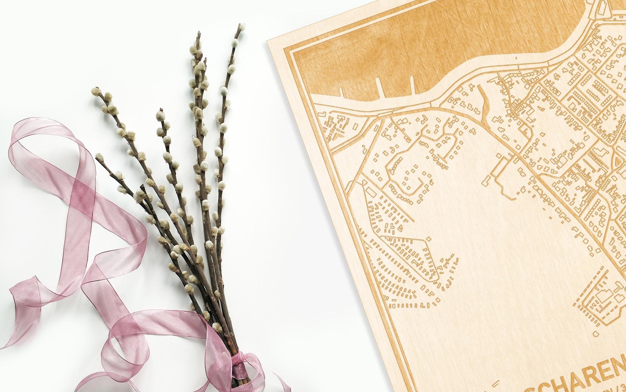 Hier ligt de houten plattegrond Scharendijke naast een bloemetje als gepersonaliseerd cadeau voor haar.
