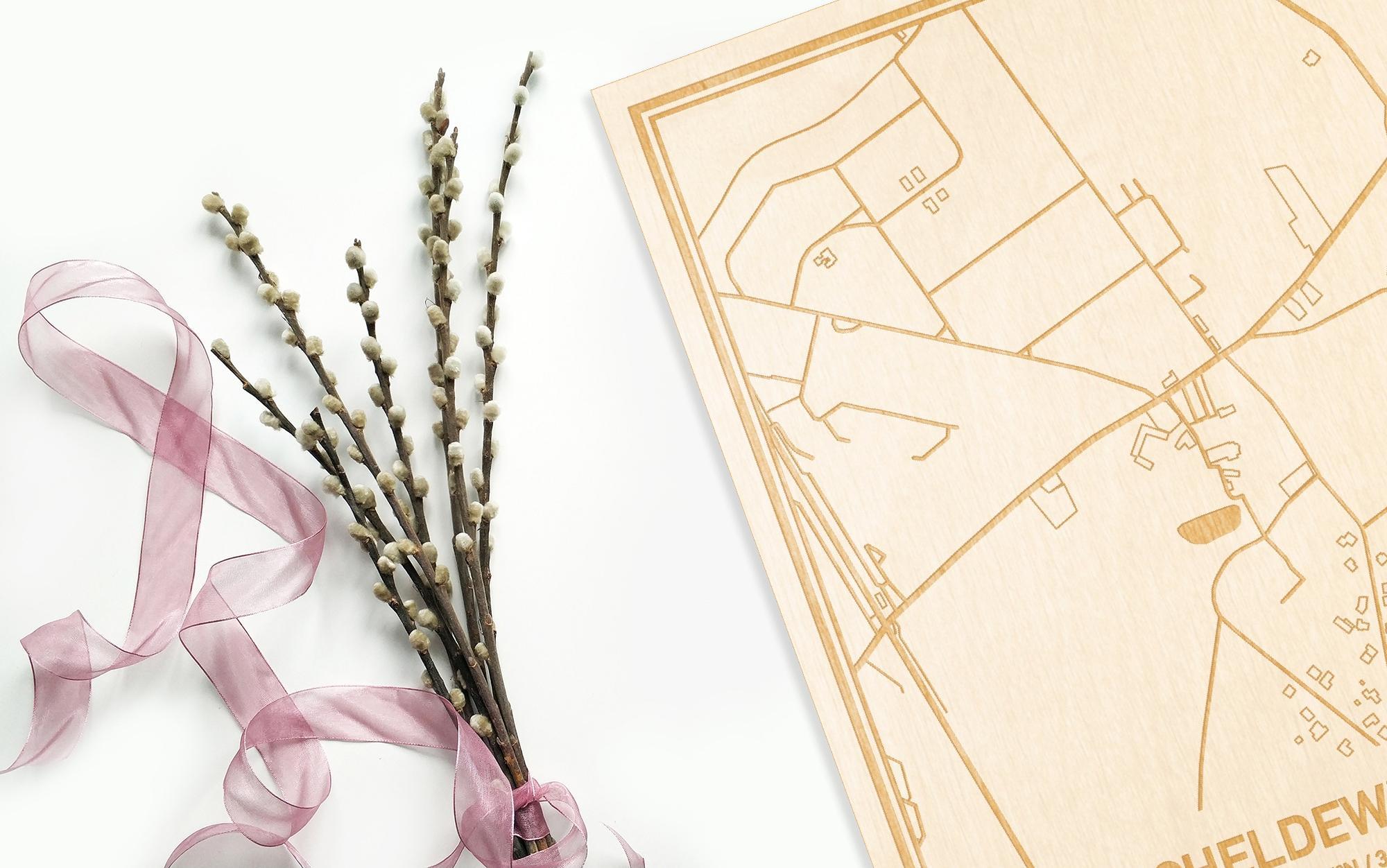 Hier ligt de houten plattegrond Scheldewindeke naast een bloemetje als gepersonaliseerd cadeau voor haar.