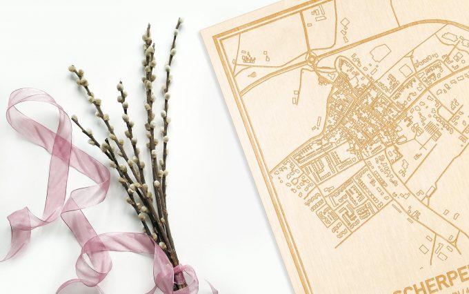 Hier ligt de houten plattegrond Scherpenisse naast een bloemetje als gepersonaliseerd cadeau voor haar.