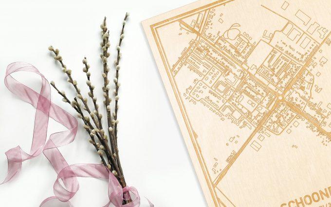 Hier ligt de houten plattegrond Schoondijke naast een bloemetje als gepersonaliseerd cadeau voor haar.