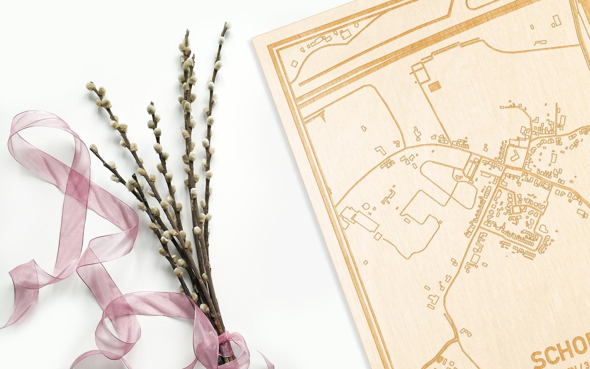 Hier ligt de houten plattegrond Schore naast een bloemetje als gepersonaliseerd cadeau voor haar.