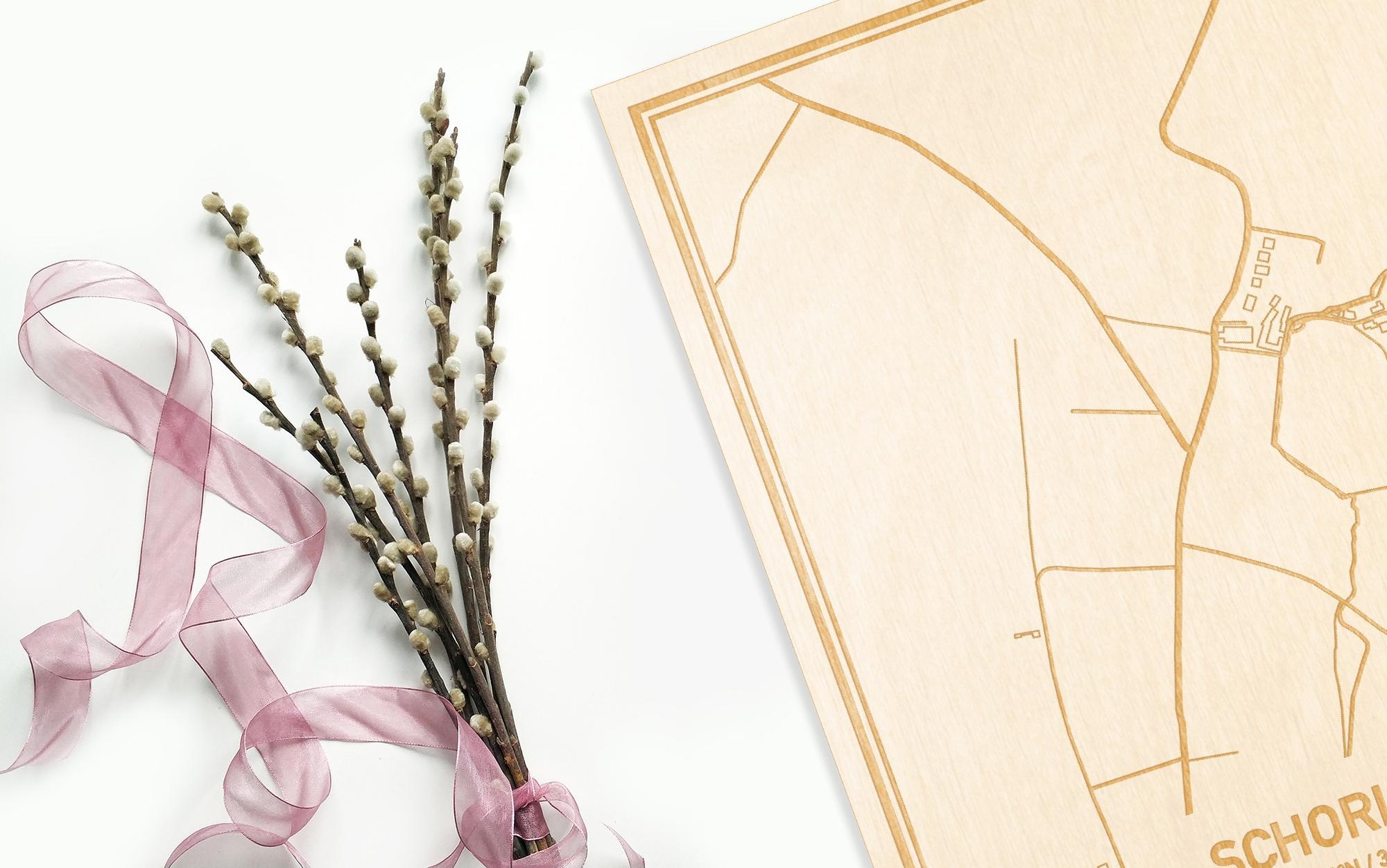 Hier ligt de houten plattegrond Schorisse naast een bloemetje als gepersonaliseerd cadeau voor haar.
