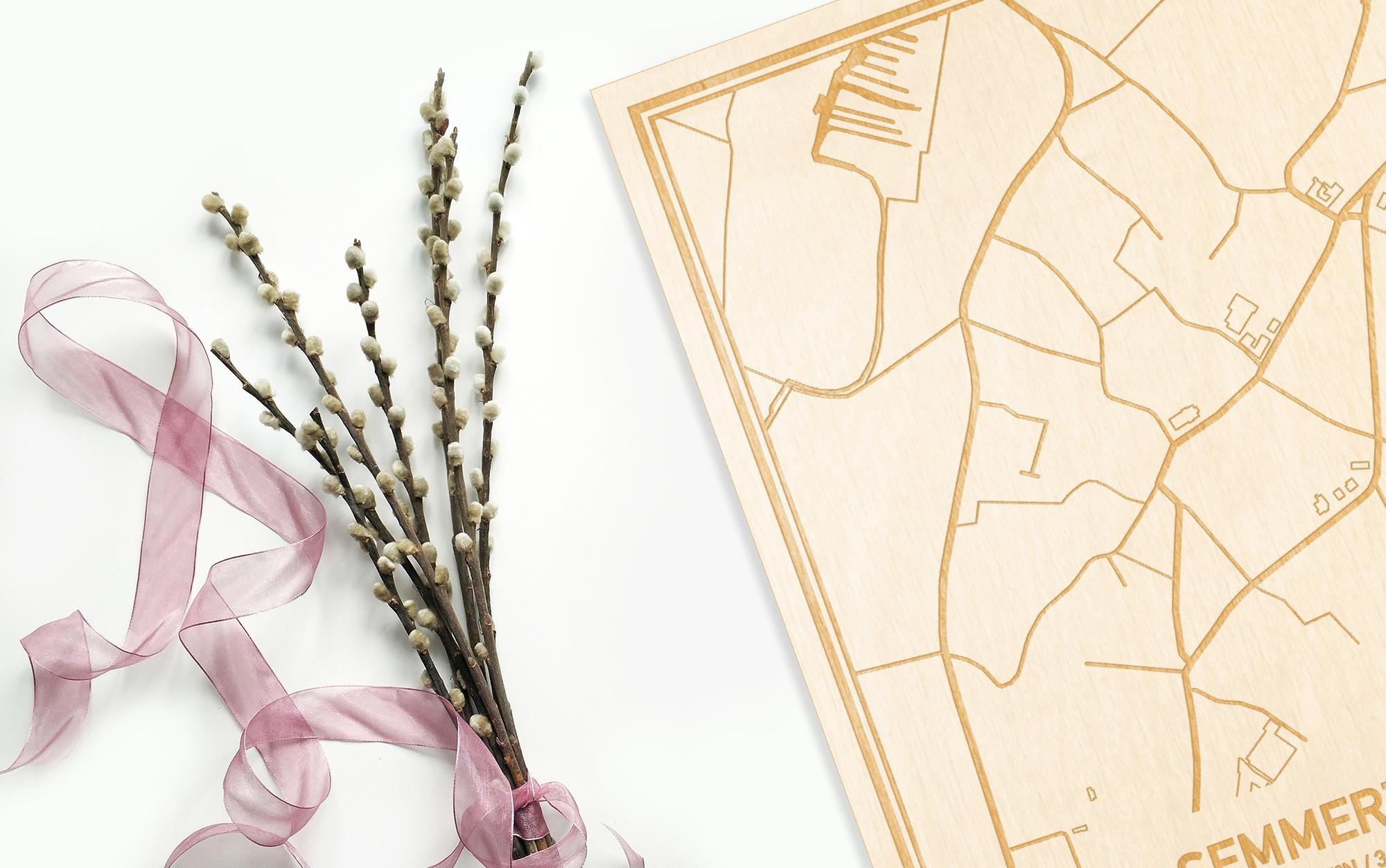 Hier ligt de houten plattegrond Semmerzake naast een bloemetje als gepersonaliseerd cadeau voor haar.