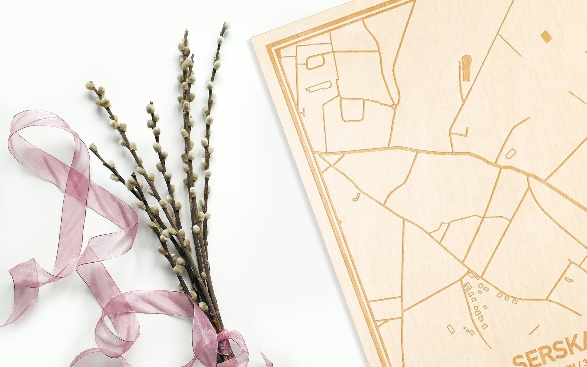 Hier ligt de houten plattegrond Serskamp naast een bloemetje als gepersonaliseerd cadeau voor haar.