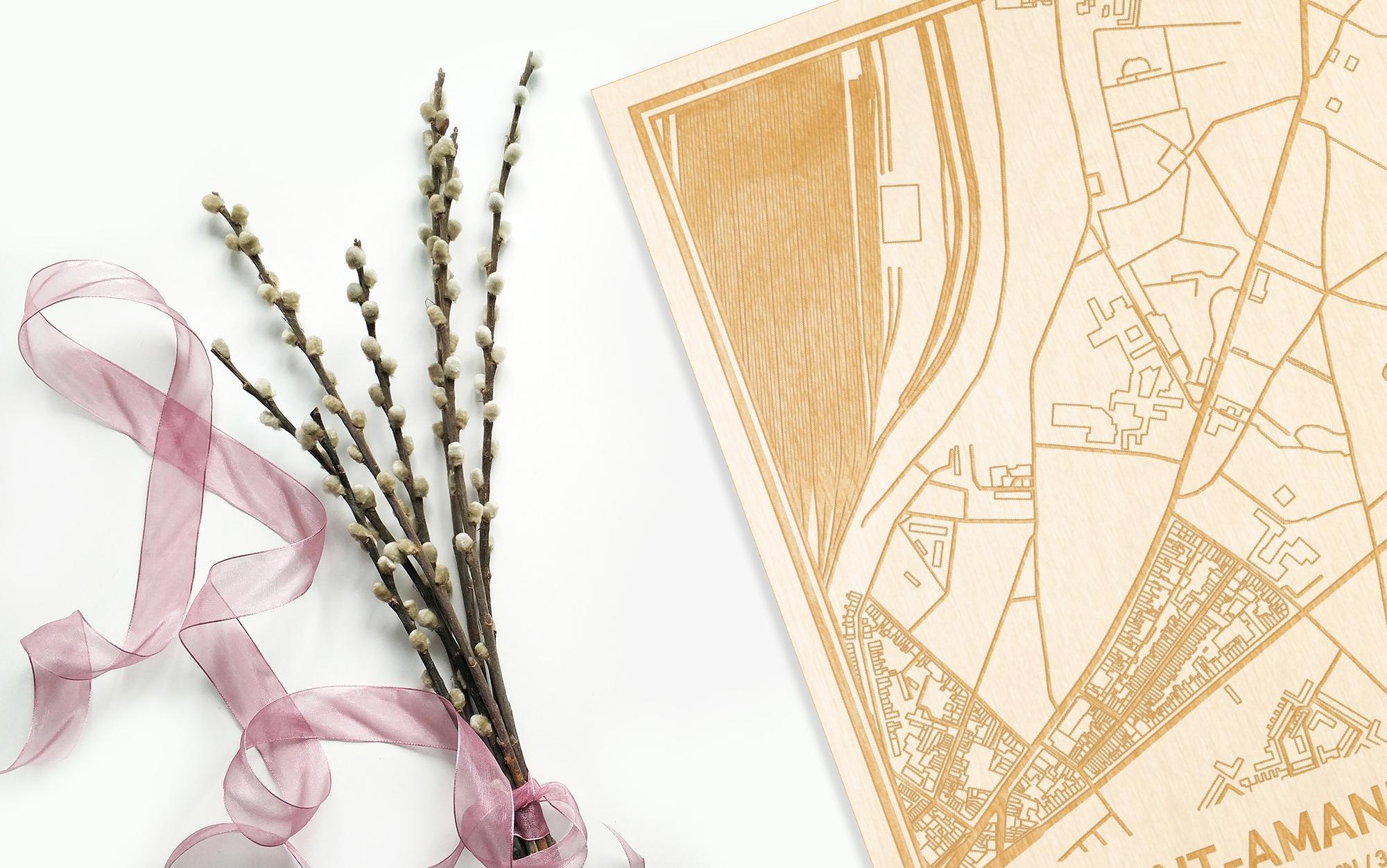 Hier ligt de houten plattegrond Sint-Amandsberg naast een bloemetje als gepersonaliseerd cadeau voor haar.
