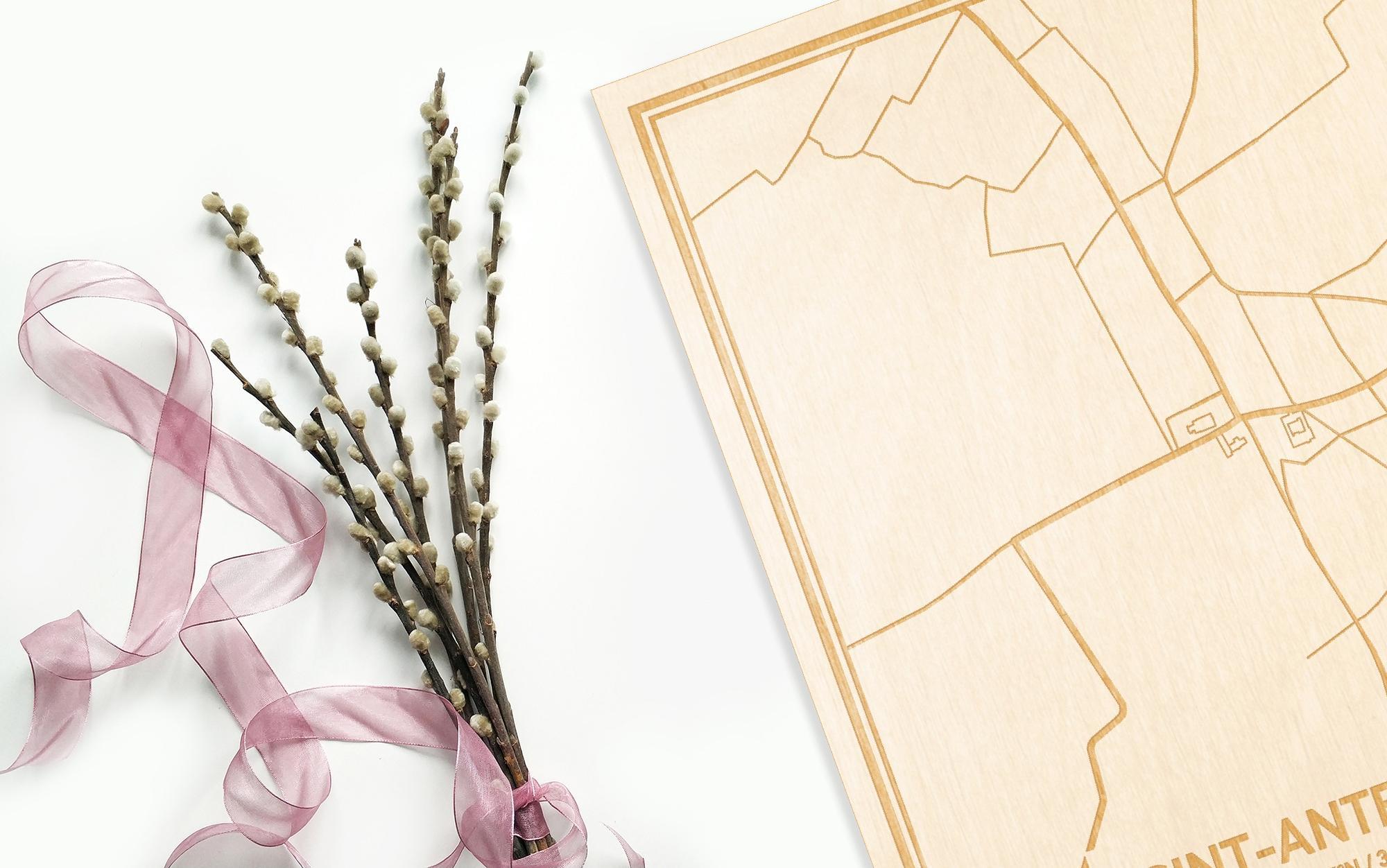 Hier ligt de houten plattegrond Sint-Antelinks naast een bloemetje als gepersonaliseerd cadeau voor haar.