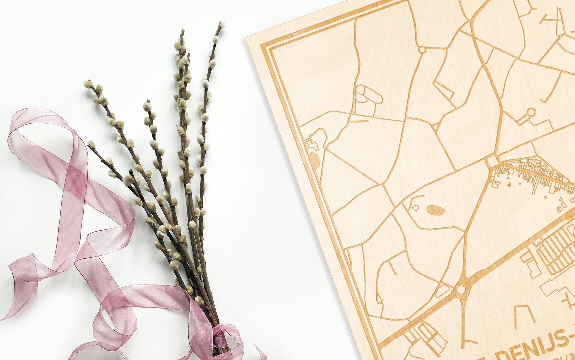 Hier ligt de houten plattegrond Sint-Denijs-Westrem naast een bloemetje als gepersonaliseerd cadeau voor haar.
