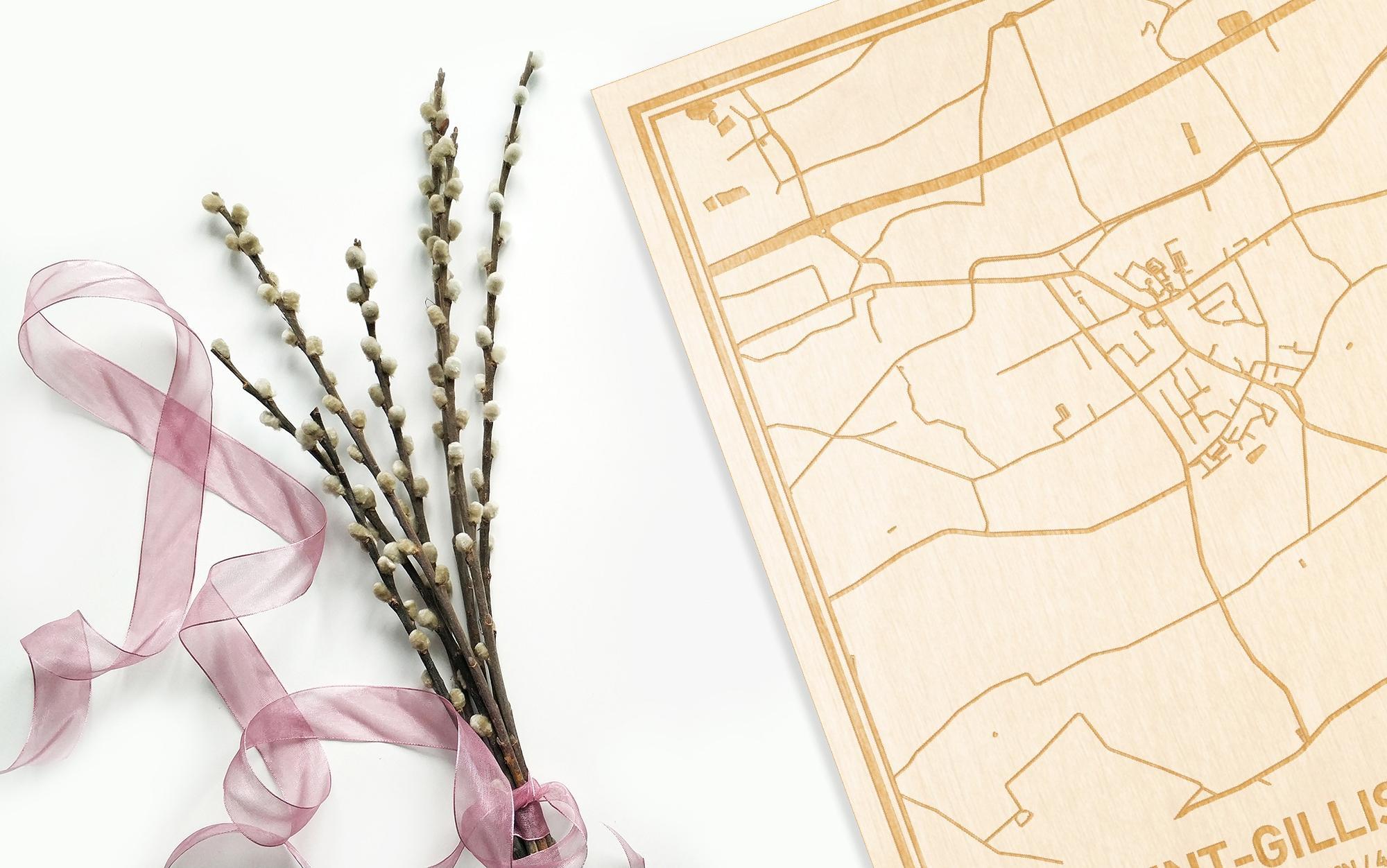Hier ligt de houten plattegrond Sint-Gillis-Waas naast een bloemetje als gepersonaliseerd cadeau voor haar.