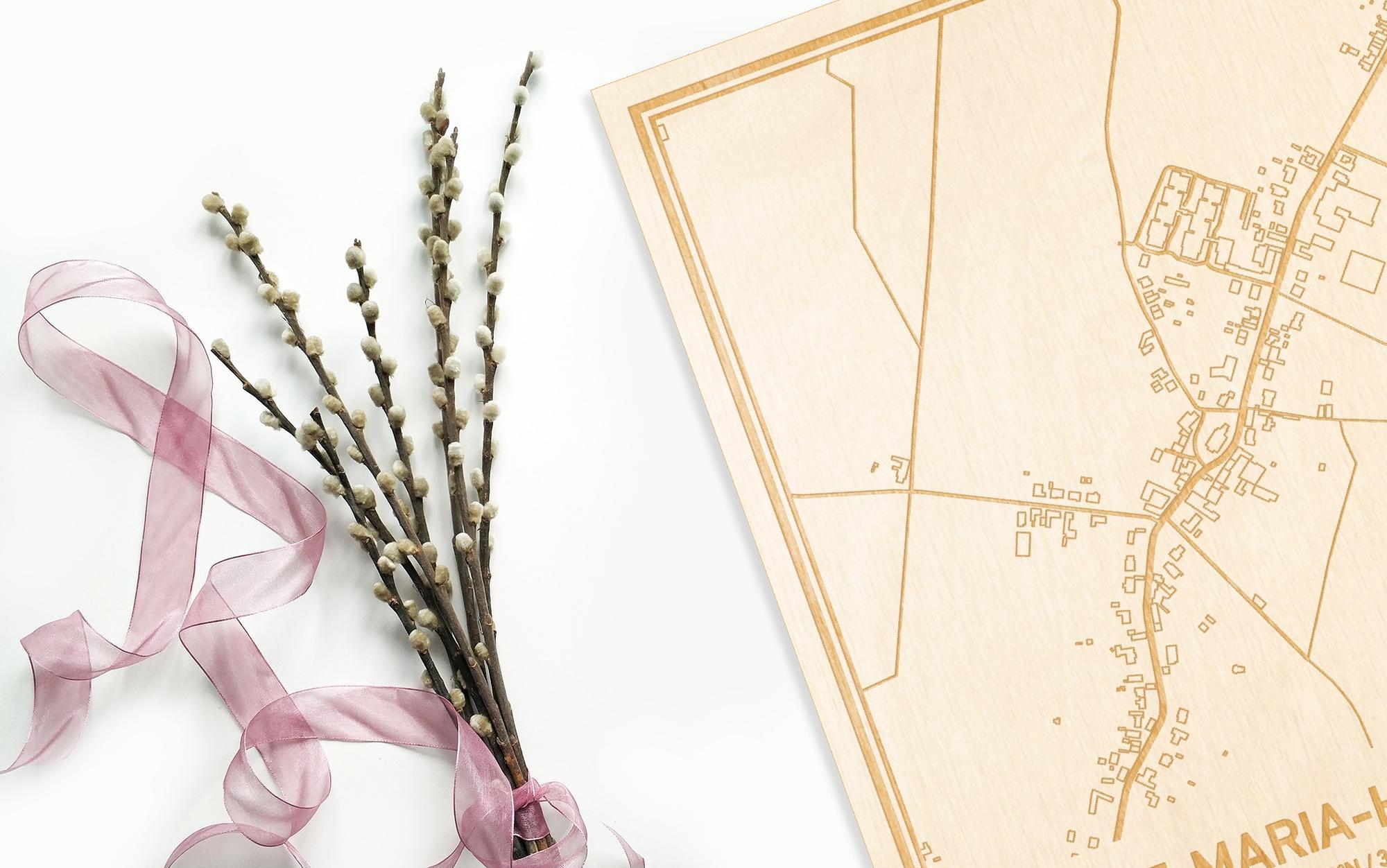 Hier ligt de houten plattegrond Sint-Maria-Horebeke naast een bloemetje als gepersonaliseerd cadeau voor haar.