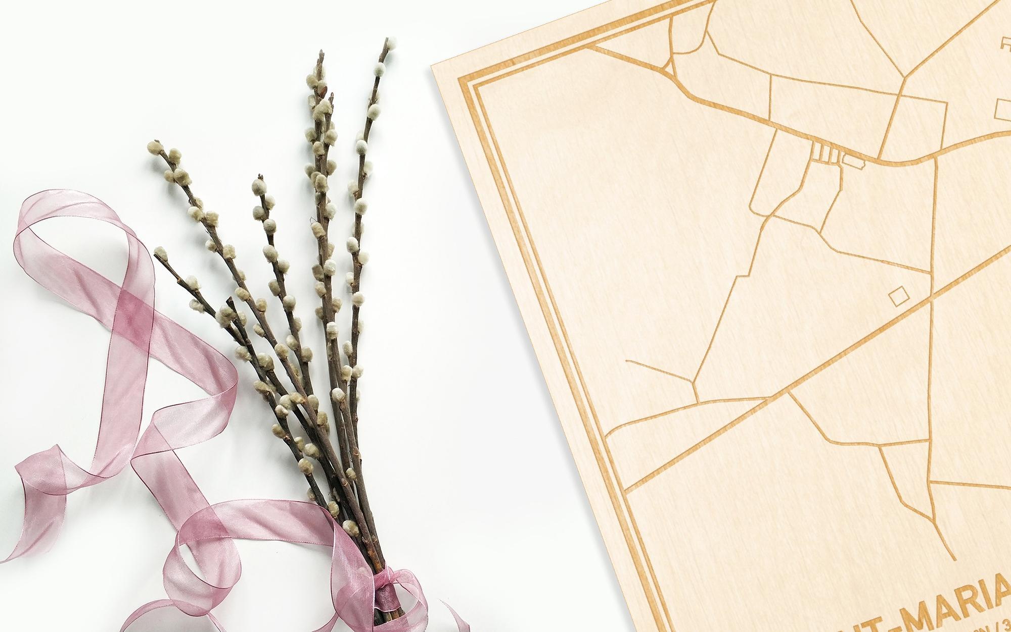 Hier ligt de houten plattegrond Sint-Maria-Lierde naast een bloemetje als gepersonaliseerd cadeau voor haar.