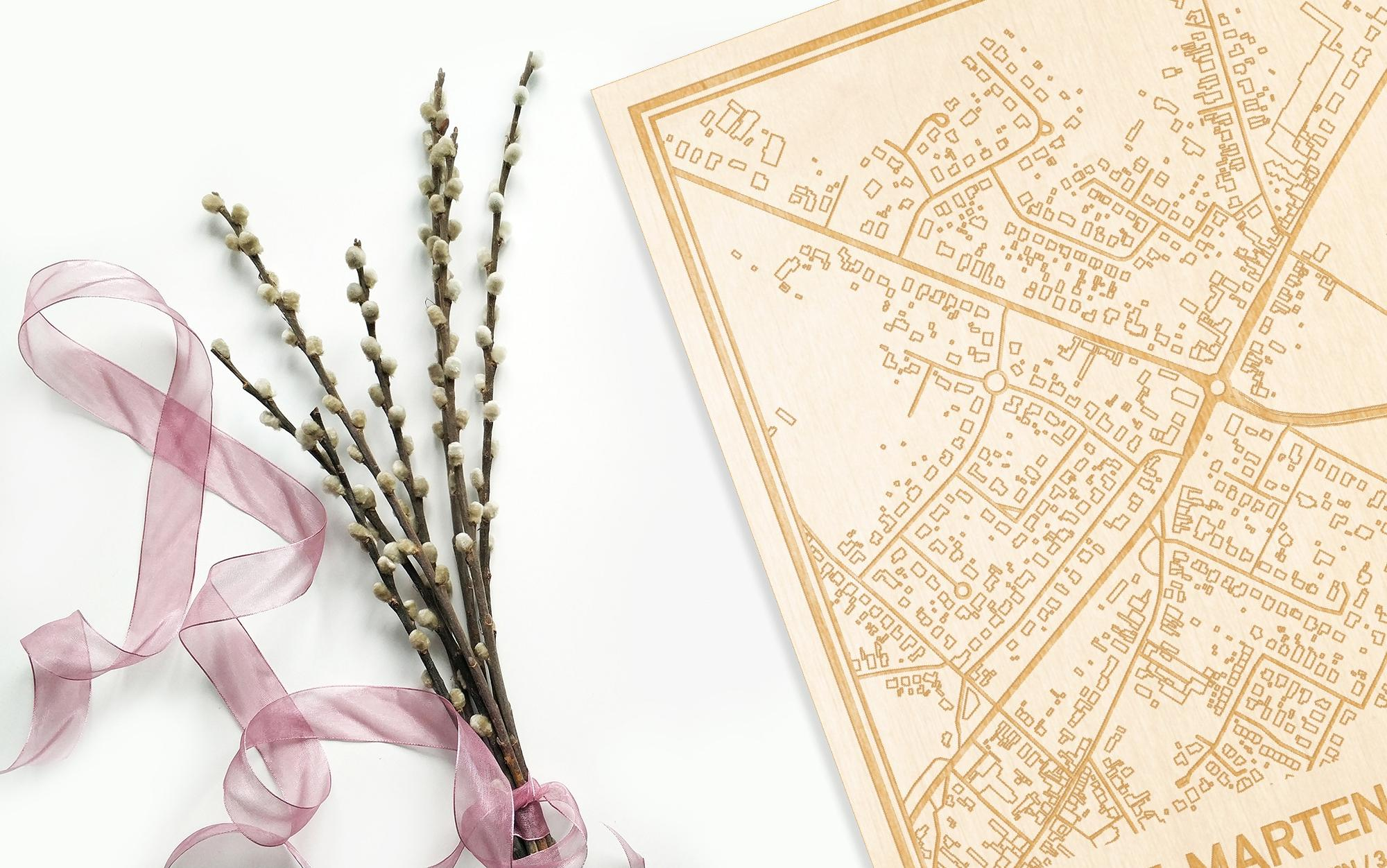 Hier ligt de houten plattegrond Sint-Martens-Leerne naast een bloemetje als gepersonaliseerd cadeau voor haar.