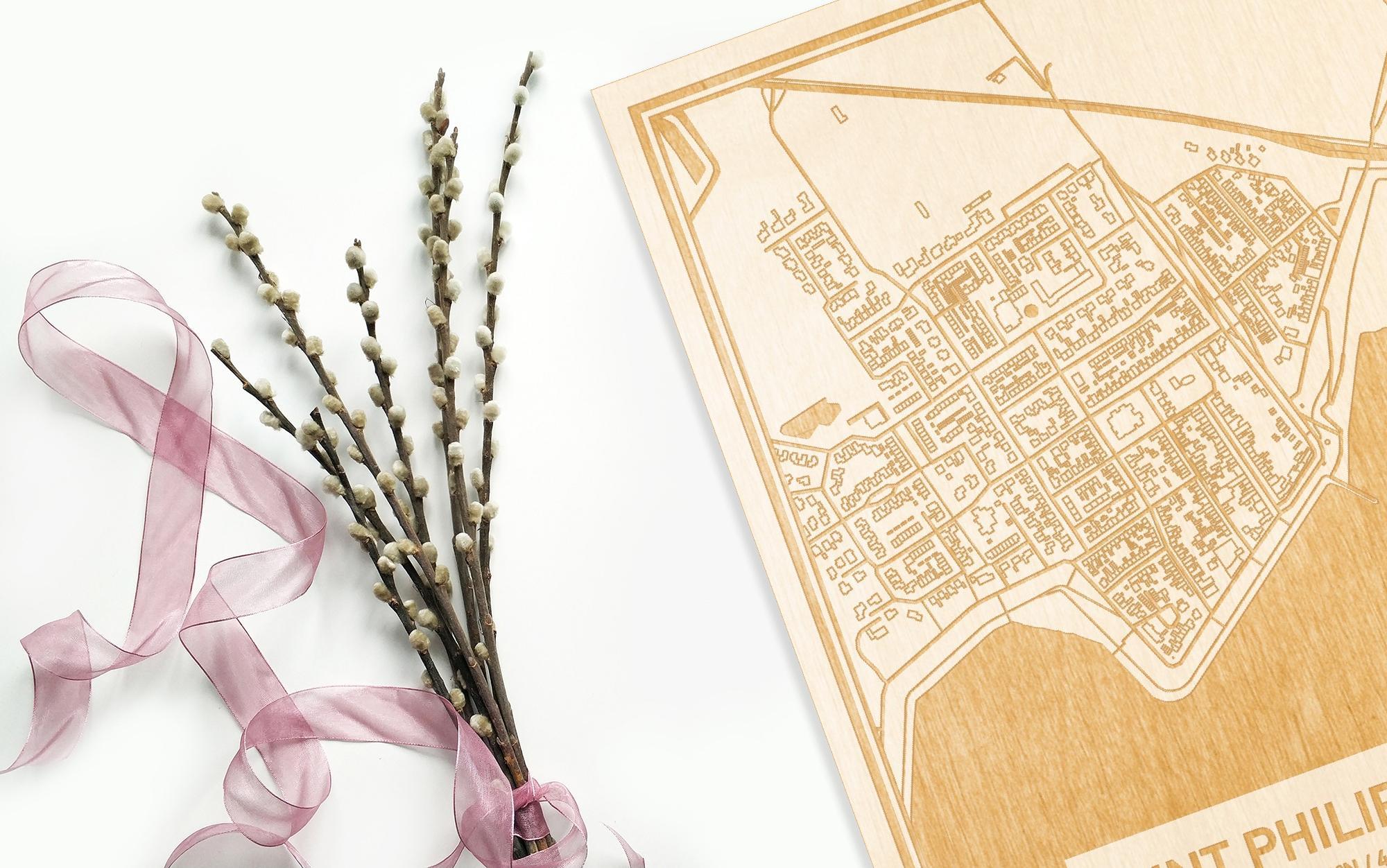 Hier ligt de houten plattegrond Sint Philipsland naast een bloemetje als gepersonaliseerd cadeau voor haar.