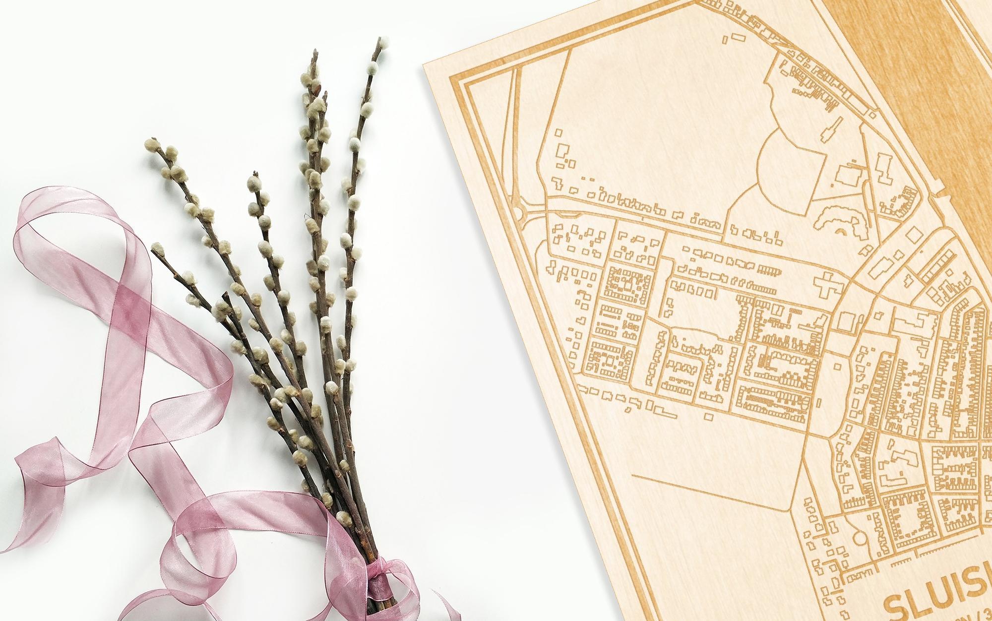 Hier ligt de houten plattegrond Sluiskil naast een bloemetje als gepersonaliseerd cadeau voor haar.