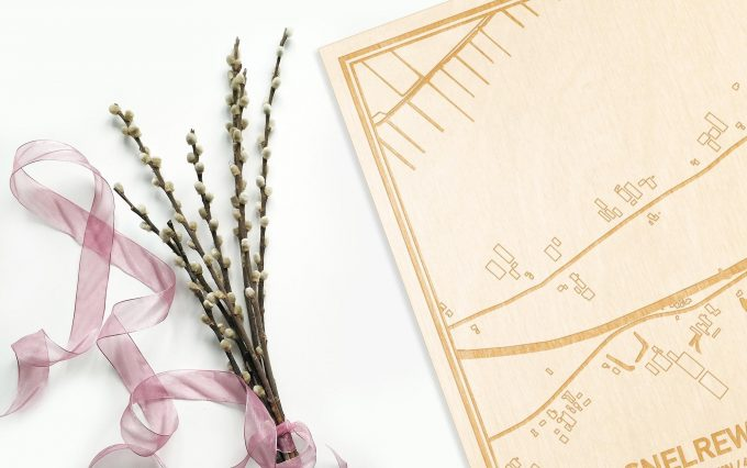 Hier ligt de houten plattegrond Snelrewaard naast een bloemetje als gepersonaliseerd cadeau voor haar.