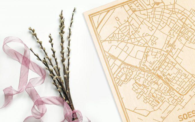 Hier ligt de houten plattegrond Soest naast een bloemetje als gepersonaliseerd cadeau voor haar.