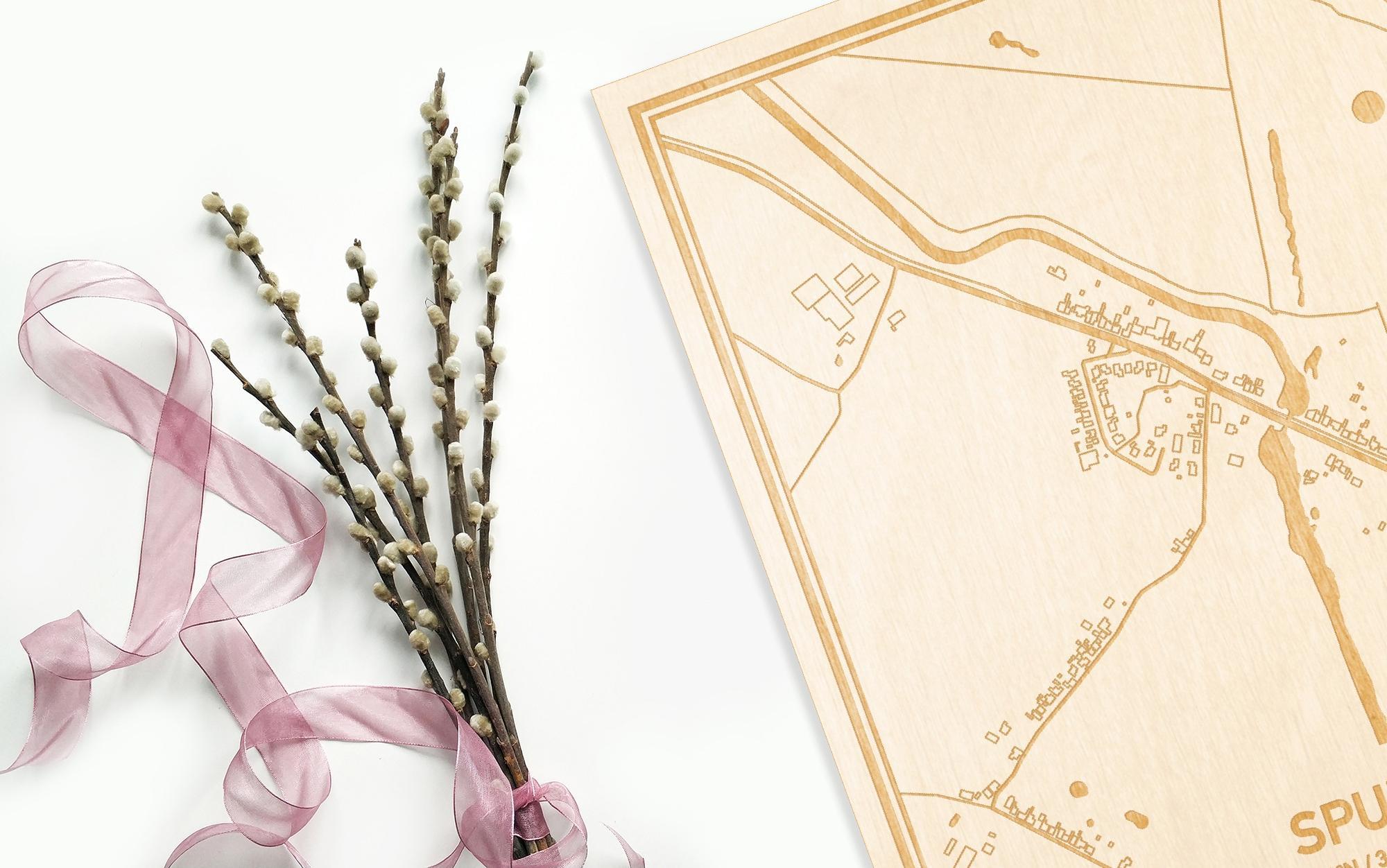 Hier ligt de houten plattegrond Spui naast een bloemetje als gepersonaliseerd cadeau voor haar.