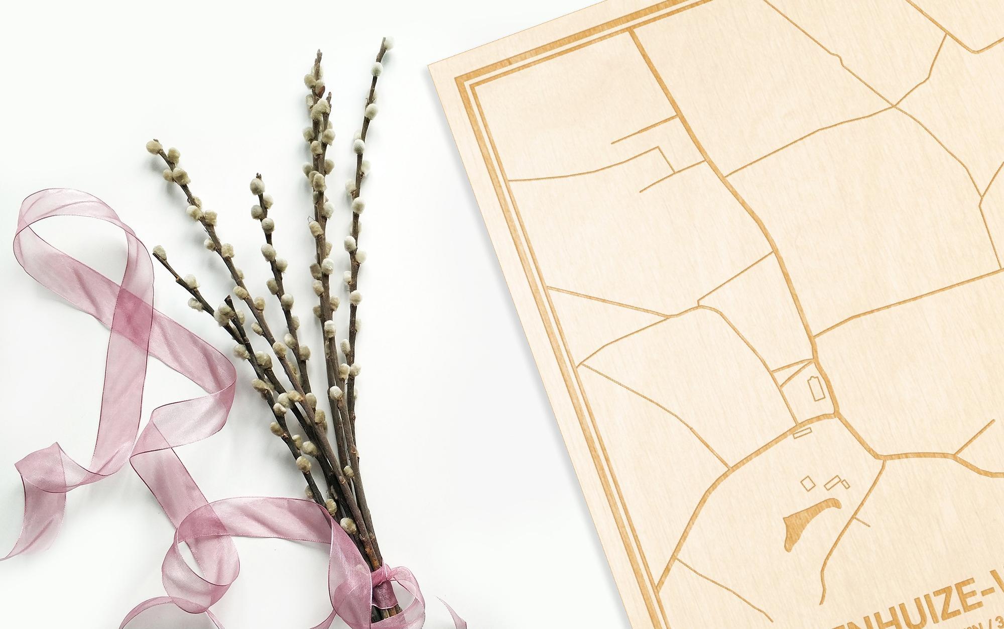 Hier ligt de houten plattegrond Steenhuize-Wijnhuize naast een bloemetje als gepersonaliseerd cadeau voor haar.
