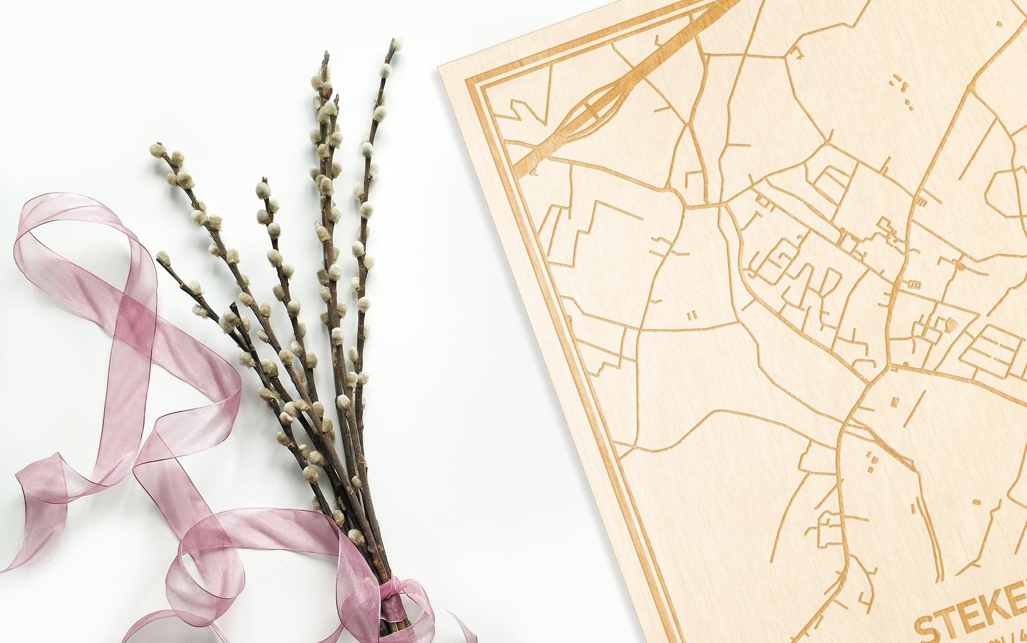 Hier ligt de houten plattegrond Stekene naast een bloemetje als gepersonaliseerd cadeau voor haar.