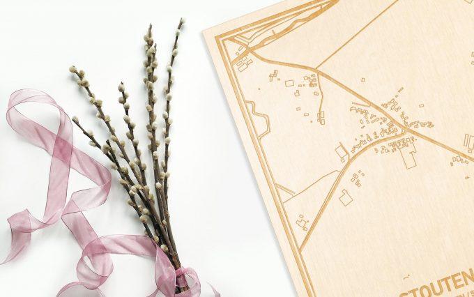 Hier ligt de houten plattegrond Stoutenburg naast een bloemetje als gepersonaliseerd cadeau voor haar.