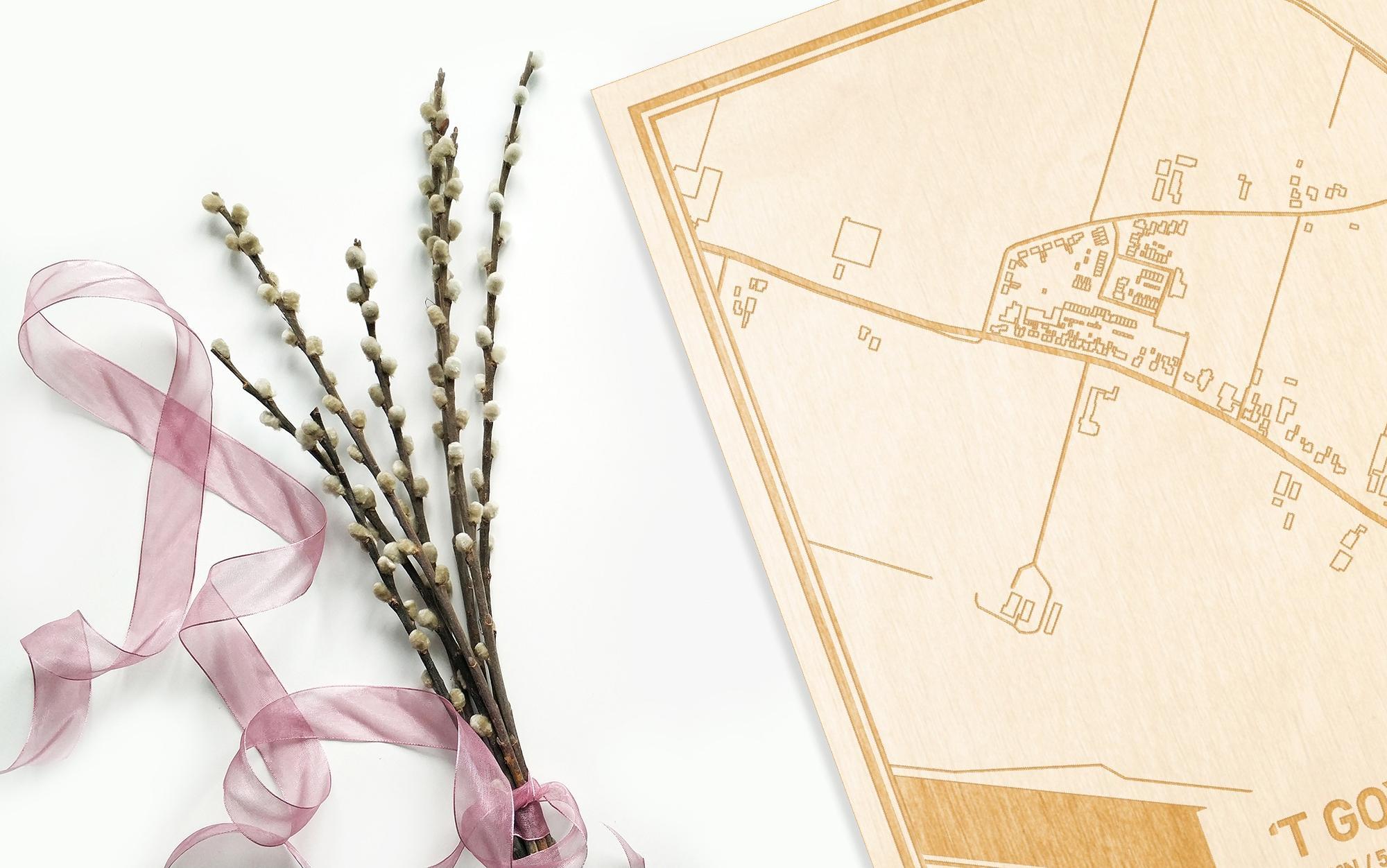 Hier ligt de houten plattegrond 't Goy naast een bloemetje als gepersonaliseerd cadeau voor haar.