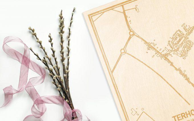 Hier ligt de houten plattegrond Terhole naast een bloemetje als gepersonaliseerd cadeau voor haar.