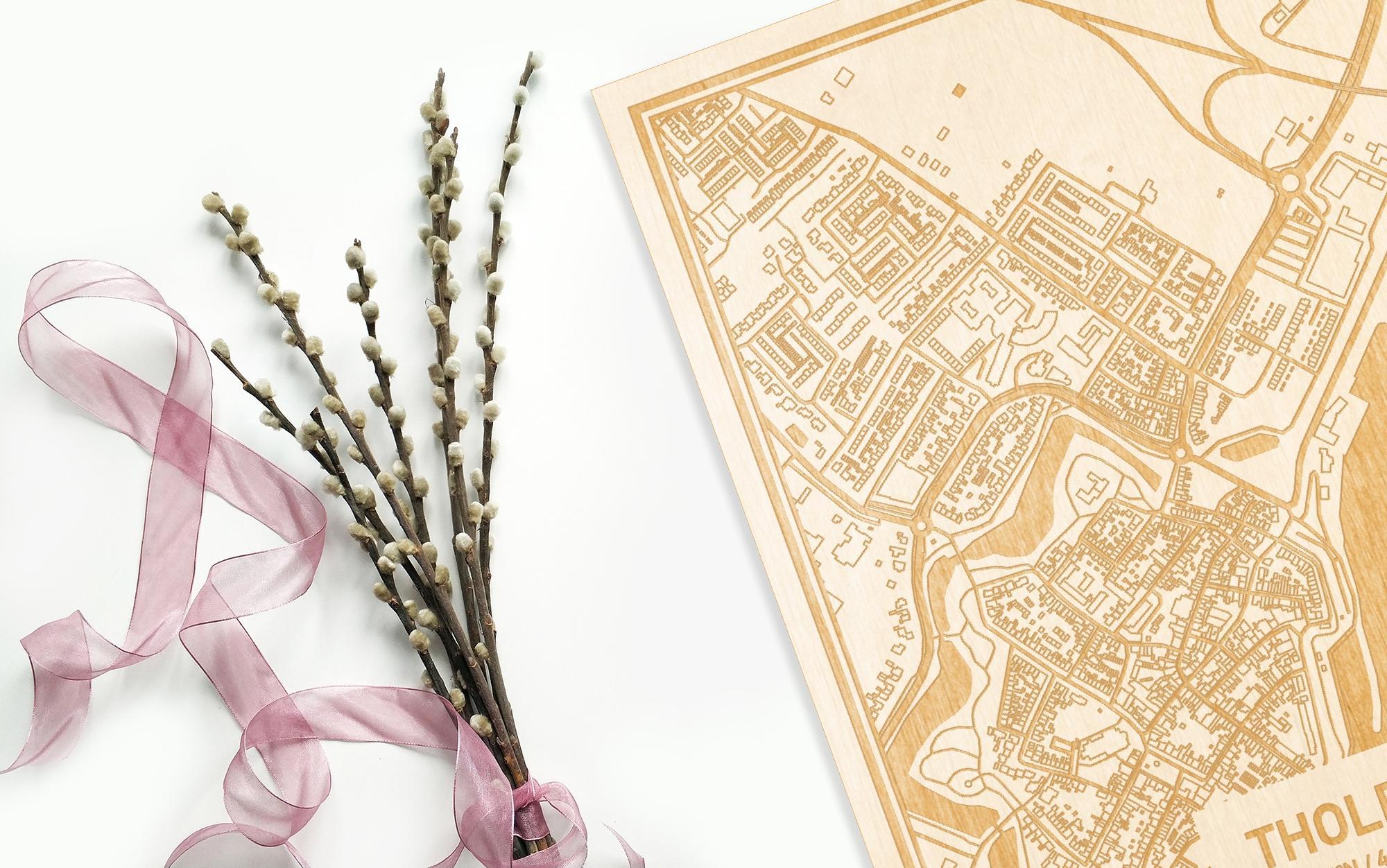 Hier ligt de houten plattegrond Tholen naast een bloemetje als gepersonaliseerd cadeau voor haar.