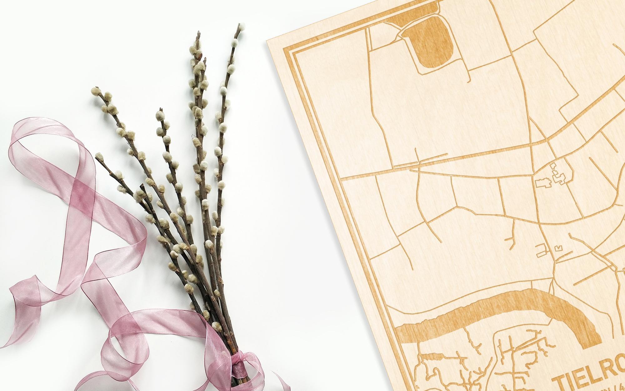 Hier ligt de houten plattegrond Tielrode naast een bloemetje als gepersonaliseerd cadeau voor haar.