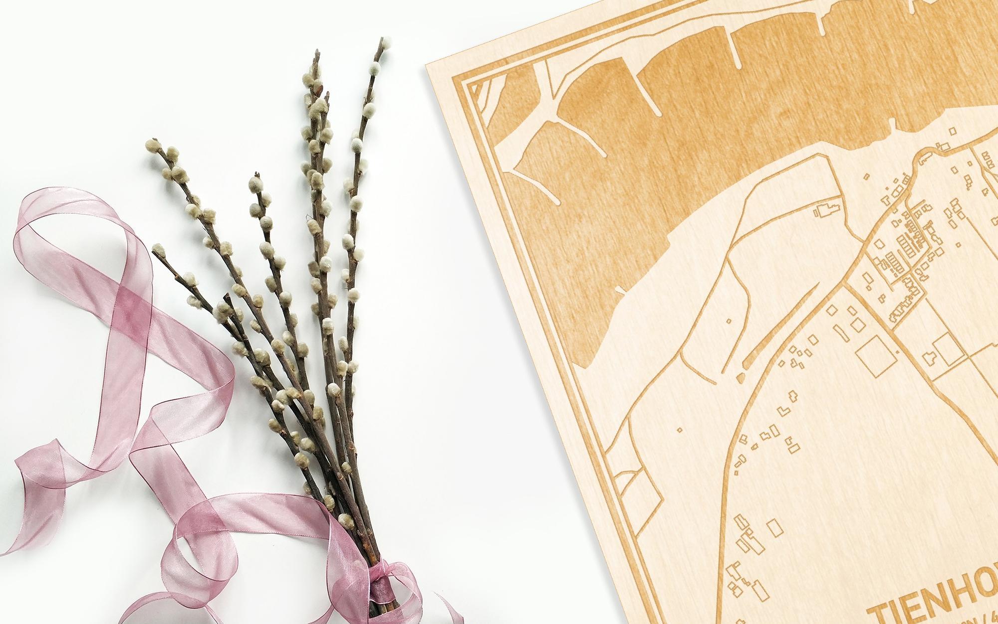 Hier ligt de houten plattegrond Tienhoven naast een bloemetje als gepersonaliseerd cadeau voor haar.